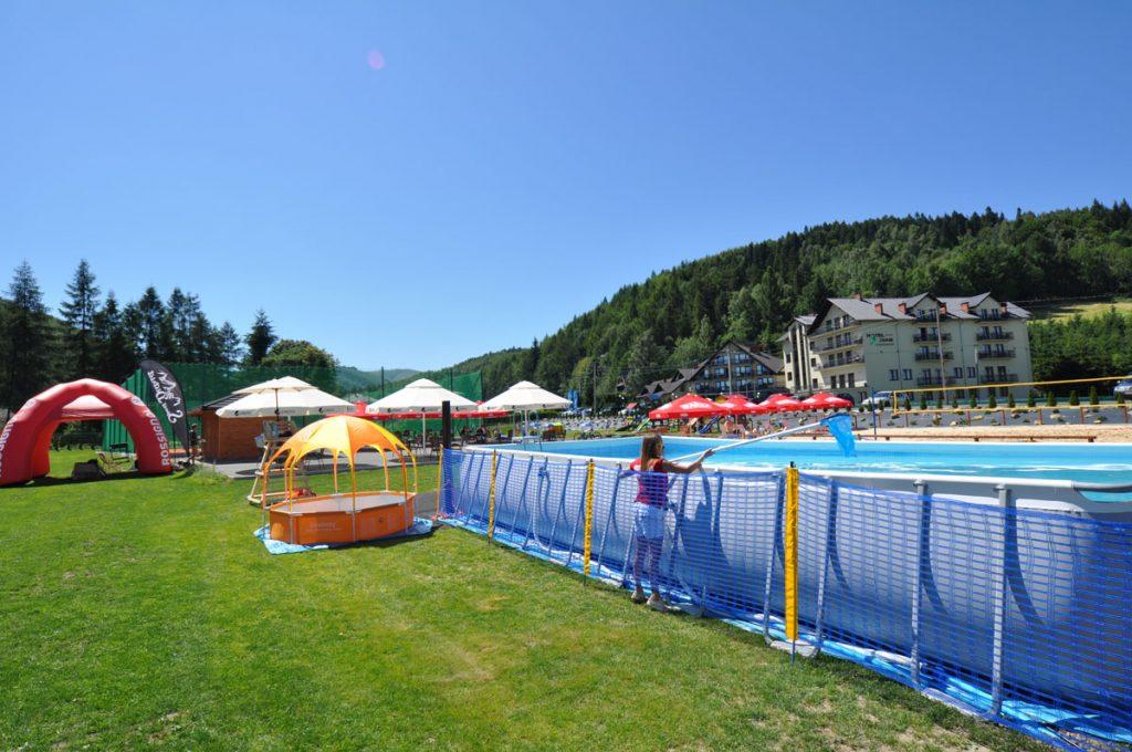 basen zewnętrzny w tle parasoli i teren rekreacyjny