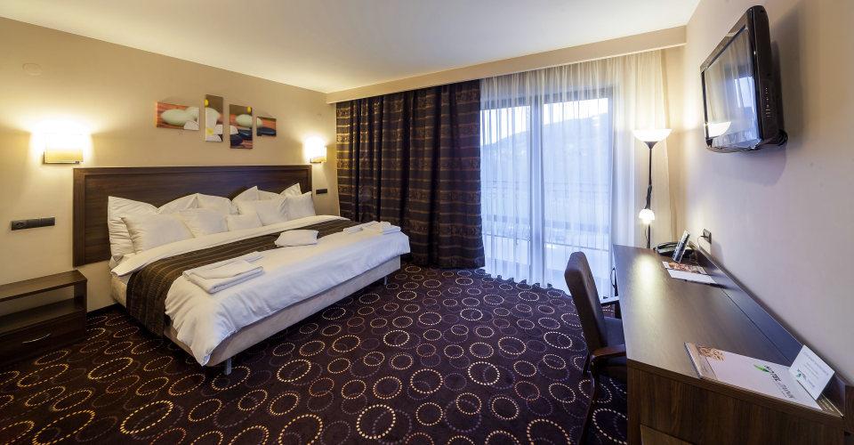pokój z biurkiem i dużym dwuosobowym łóżkiem