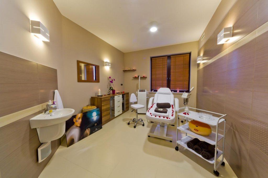 gabinet spa w berzowym wnętrzu stoi fotel do zabiegów oraz inne urządzenia